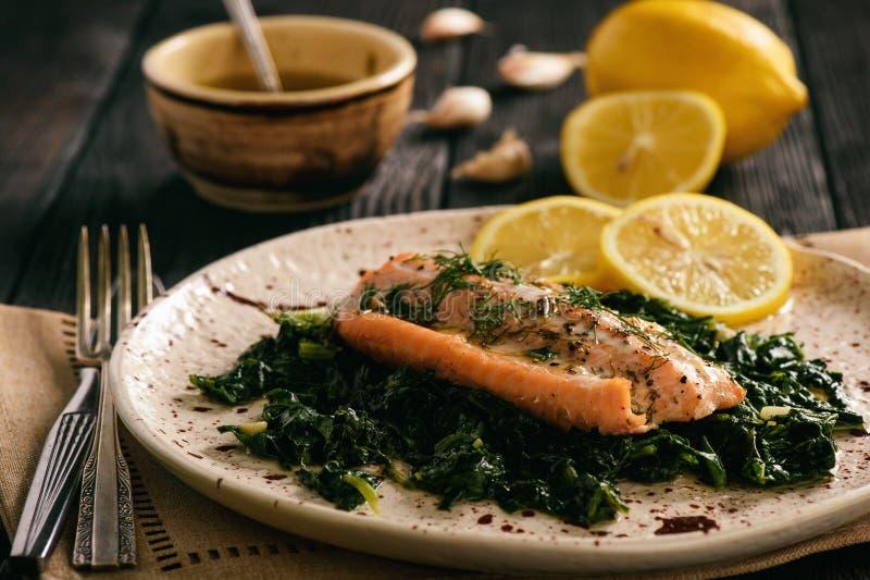 被烘烤的三文鱼在被炖的菠菜服务用柠檬奶油调味汁 免版税图库摄影