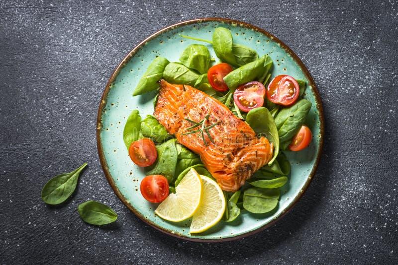 被烘烤的三文鱼鱼片有新鲜的沙拉顶视图 免版税库存照片