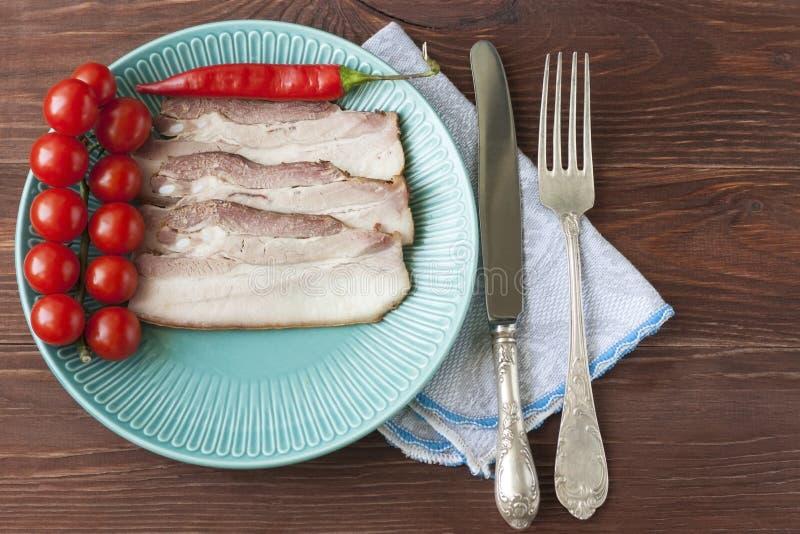 被烘烤的五花肉或烟肉切成在一块板材的薄片用蕃茄和炽热辣椒 免版税图库摄影