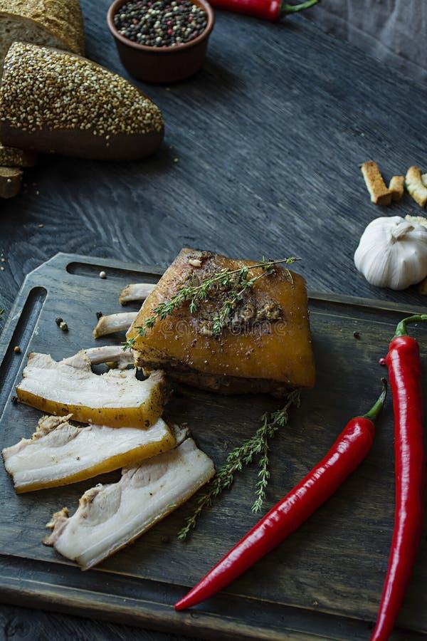 被烘烤的五花肉用香料,麝香草,苦涩胡椒,新鲜面包 乌克兰油脂 乌克兰的传统盘 黑暗木 免版税库存图片