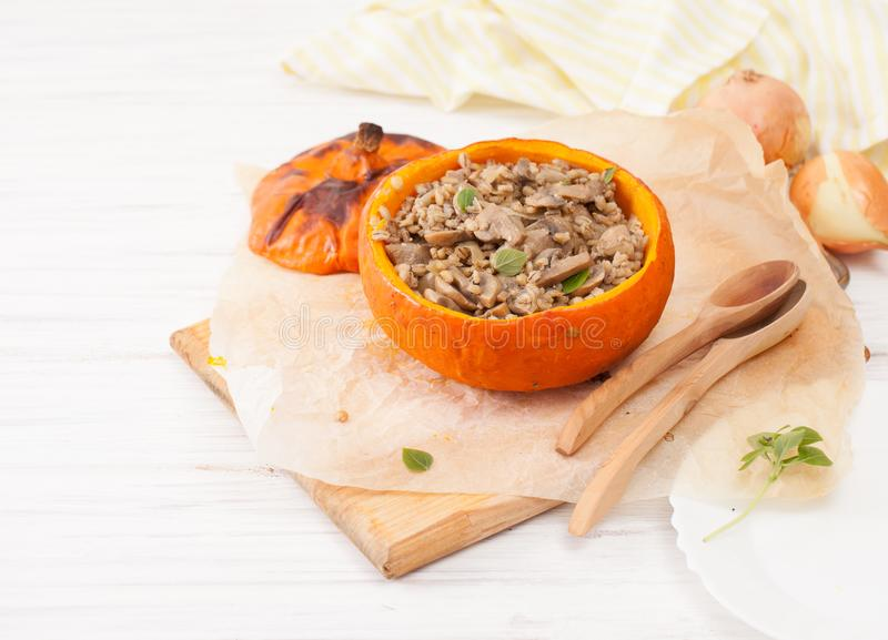 被烘烤的南瓜用蘑菇和大麦在桌上 免版税库存图片