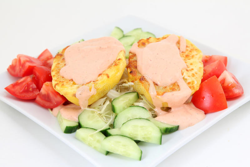 被烘烤的土豆用调味汁和菜 免版税库存图片
