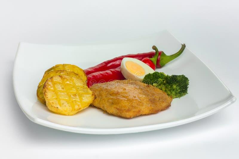 被烘烤的土豆用鸡牛排、鸡蛋和红辣椒在丝毫 图库摄影