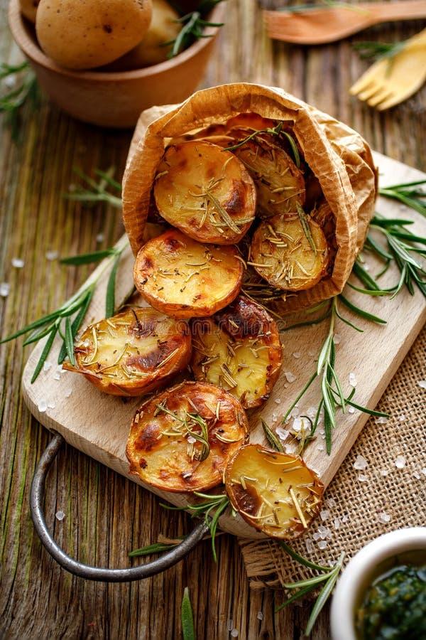 被烘烤的土豆 被烘烤的一半土豆晒干了用迷迭香和海盐在一张木土气桌上 素食食物 免版税库存照片