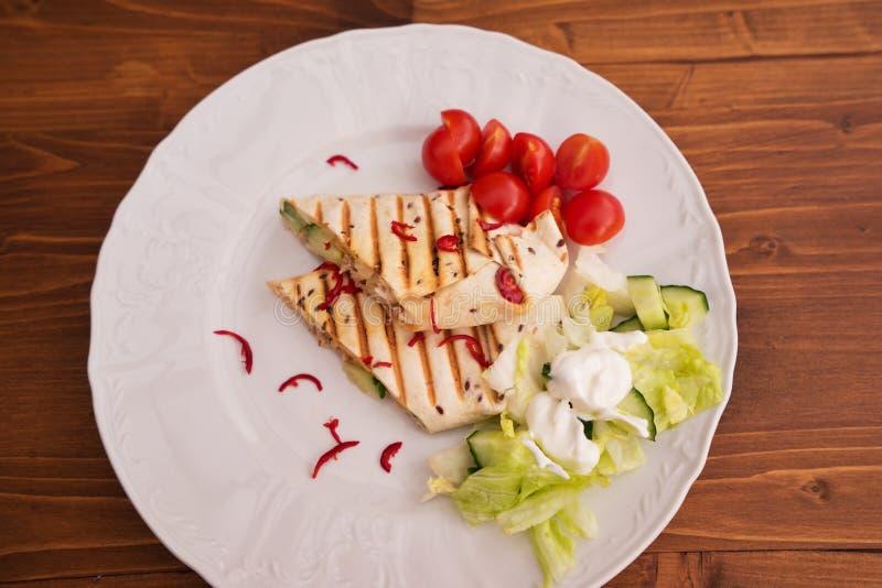 被烘烤的套的详细的图片、fachitas或者面卷饼与新辣椒片,西红柿和新鲜的沙拉与奶油 库存图片