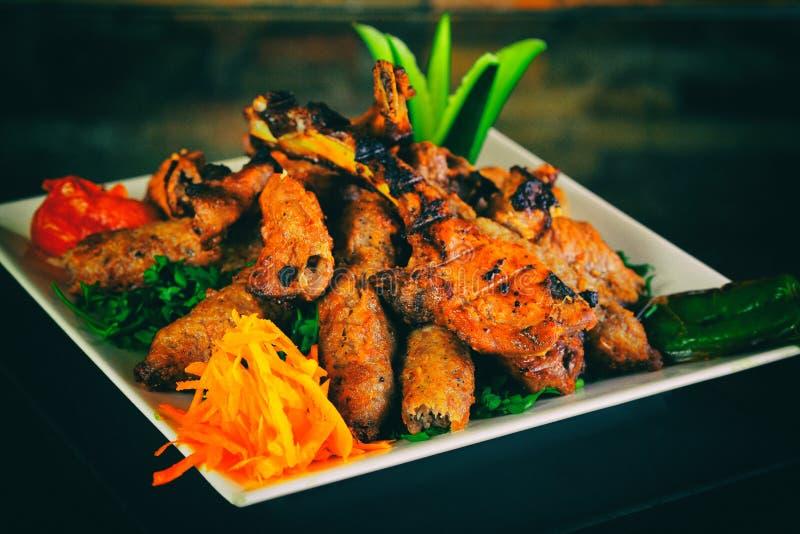 被烘烤的整鸡用桔子和土豆在板材 水平的看法从上面 免版税库存照片