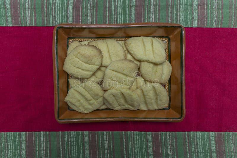 被烘烤的曲奇饼的图象在黏土碗的在一张红色和绿色圣诞节桌布 库存图片