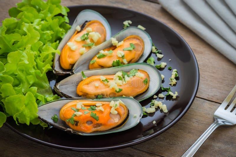 被烘烤的淡菜用在板材的大蒜 免版税图库摄影