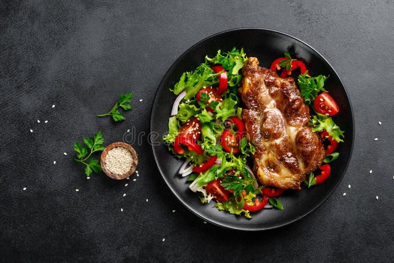被烘烤的猪肉牛排用新鲜蔬菜沙拉 库存照片