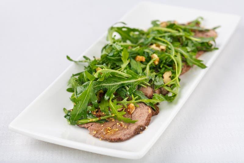 被烘烤的肉用调味汁和新鲜的草本 图库摄影
