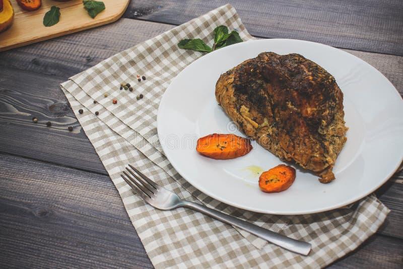 被烘烤的肉静物画一个大片断在一张轻的木桌上的 免版税图库摄影