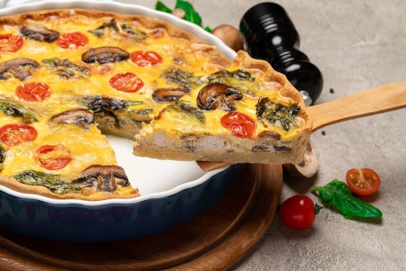 被烘烤的自创乳蛋饼在木桨的饼以陶瓷烘烤的形式和切片 图库摄影