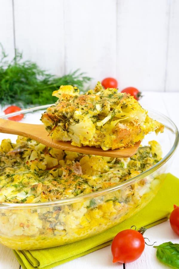 被烘烤的花椰菜用乳酪和鸡蛋以玻璃形式在白色木背景 免版税图库摄影