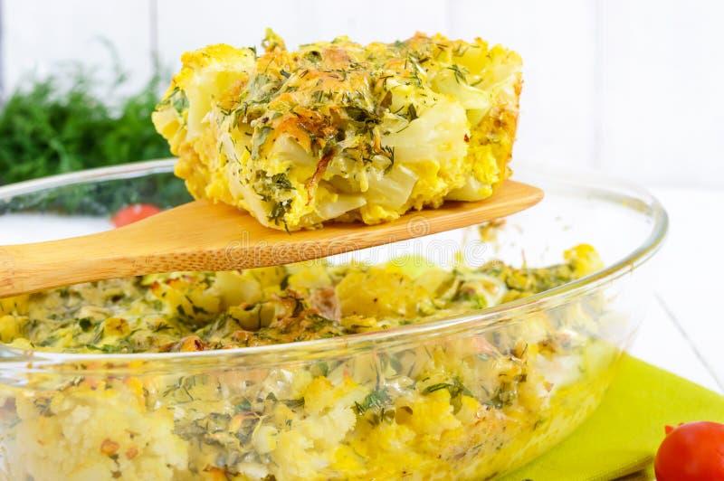 被烘烤的花椰菜用乳酪和鸡蛋以玻璃形式在白色木背景 库存图片