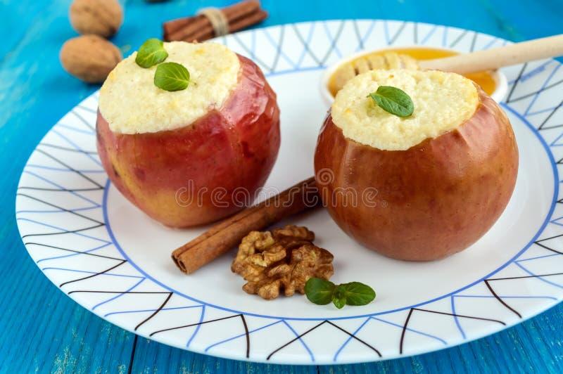 被烘烤的苹果充塞用酸奶干酪、桂香、核桃用蜂蜜和薄菏在蓝色木背景 免版税库存照片