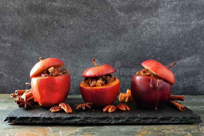 被烘烤的苹果用焦糖、红糖和和坚果在黑暗的背景 免版税库存照片