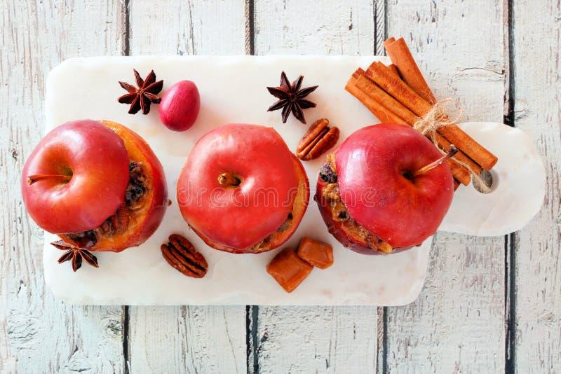 被烘烤的苹果用焦糖、红糖和和坚果,在白色木头的顶视图 免版税库存照片