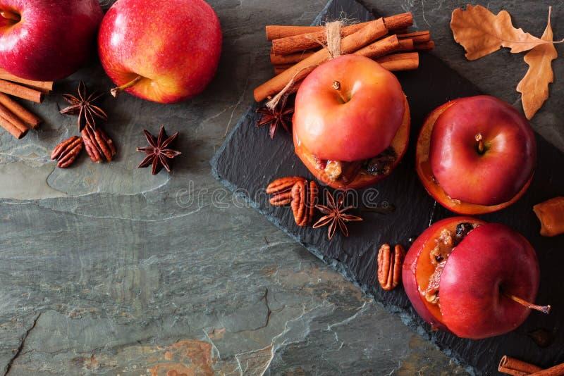 被烘烤的苹果用焦糖、红糖和和坚果,在黑暗的背景的顶视图 免版税库存照片