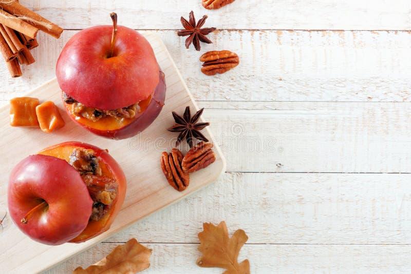 被烘烤的苹果用焦糖、红糖和和坚果,顶视图,在白色木头的旁边边界 免版税库存图片