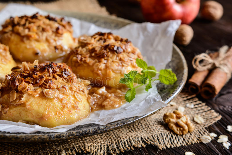 被烘烤的苹果用燕麦粥、核桃、蜂蜜和桂香 免版税图库摄影