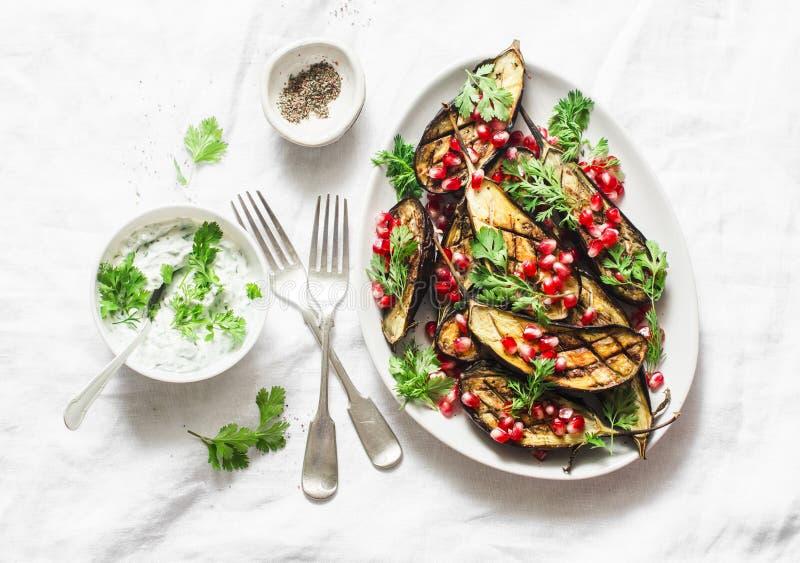 被烘烤的茄子用希脂乳、希腊酸奶、香菜调味汁和石榴种子在轻的背景,顶视图 可口快餐,塔帕纤维布 免版税库存图片