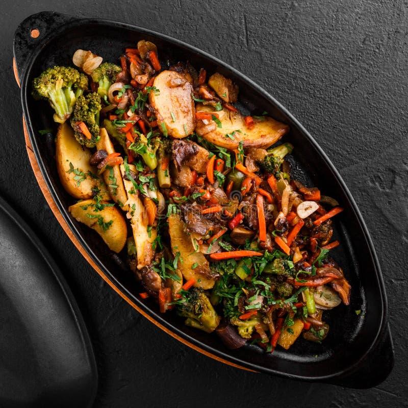 被烘烤的菜,绿色,土豆,在平底锅的硬花甘蓝在黑石背景 干净吃,健康素食主义者食物概念 免版税库存图片