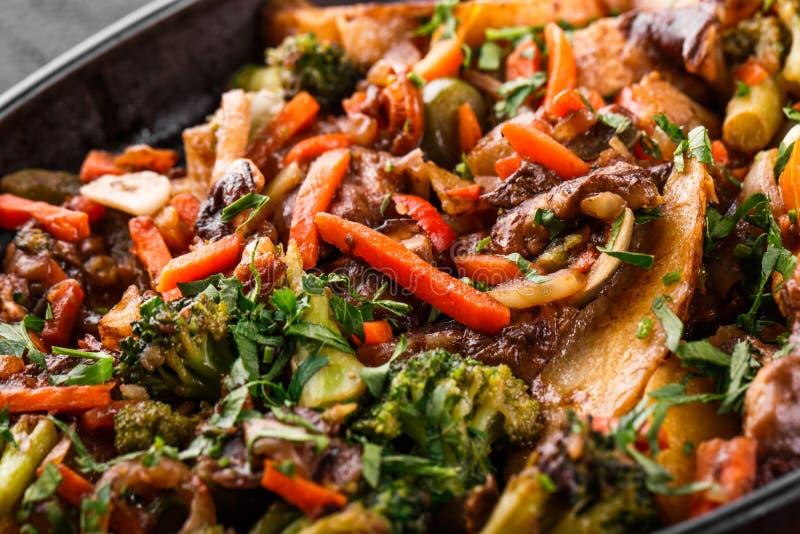 被烘烤的菜,绿色,土豆,在平底锅的硬花甘蓝在黑石背景 干净吃,健康素食主义者食物概念 库存图片