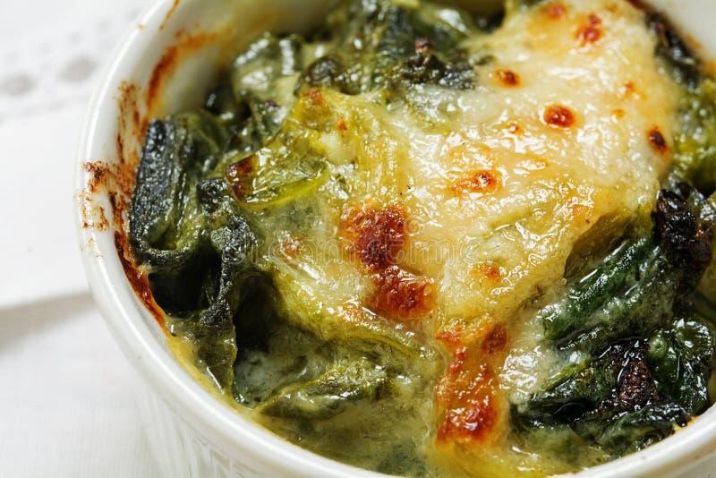 被烘烤的菠菜特写镜头与乳酪外壳的在一个小砂锅 免版税库存照片