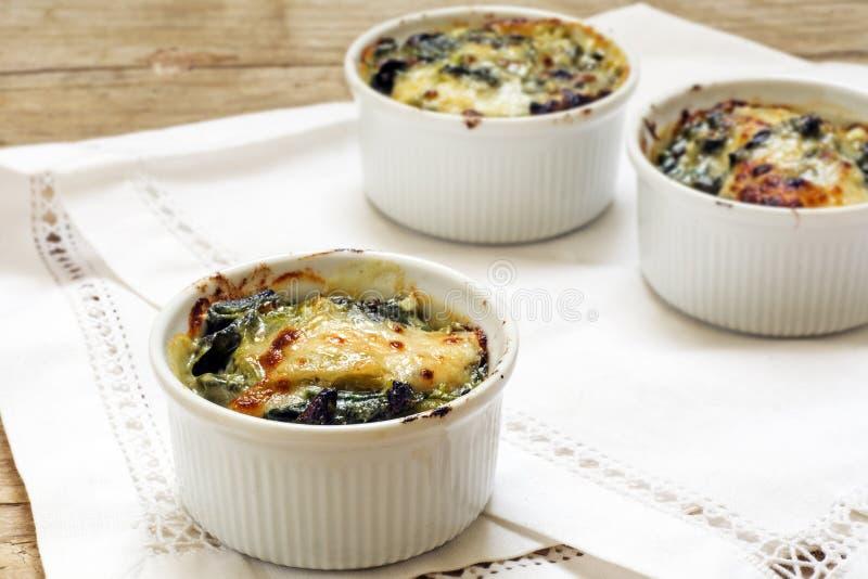 被烘烤的菠菜用在小砂锅服务的乳酪,白色休息 图库摄影