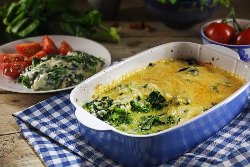 被烘烤的菠菜用ingred乳酪的巴马干酪在烘烤盘和 免版税库存图片