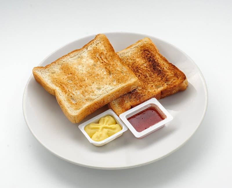 被烘烤的面包片用果酱和黄油 库存图片