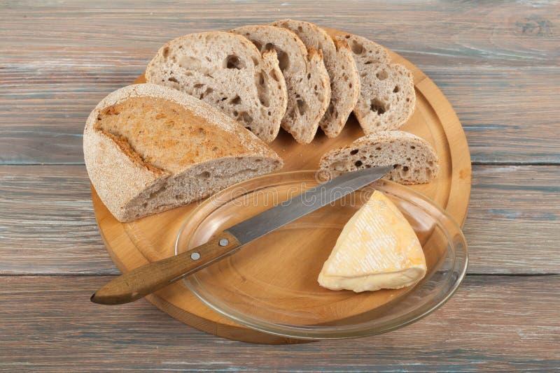 被烘烤的面包许多混杂的面包和卷在木桌背景的 图库摄影