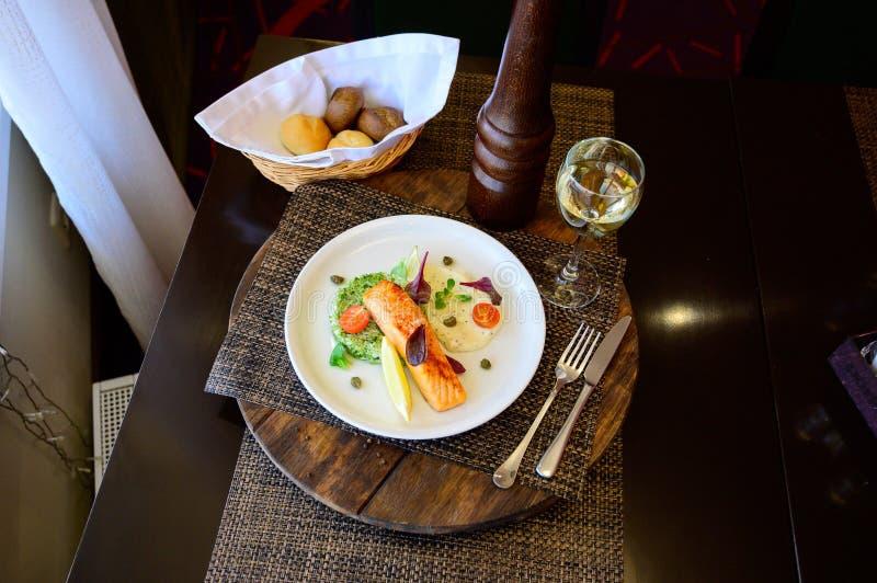 被烘烤的鱼片断用柠檬、菜和调味汁 库存图片