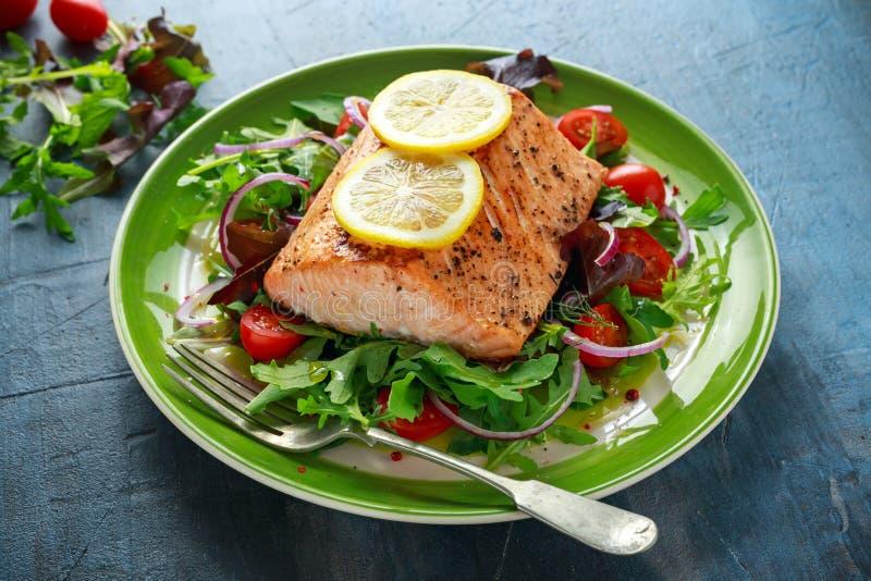 被烘烤的鲑鱼排用蕃茄,葱,绿色的混合在板材把沙拉留在 健康的食物 免版税库存照片