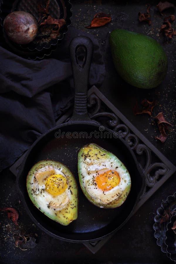 被烘烤的鲕梨用在黑暗的背景的鸡蛋 免版税图库摄影