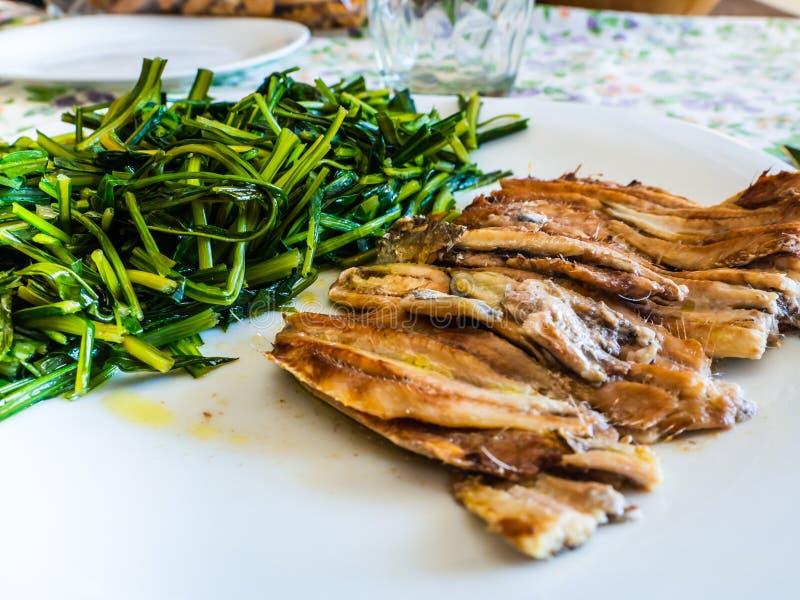 被烘烤的鲥鱼盘用苦苣生茯 免版税库存图片