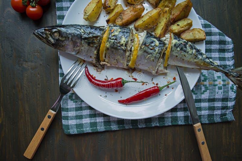 被烘烤的鲭鱼用柠檬和被烘烤的土豆在一块白色板材 r 樱桃,辣椒 ?? o 免版税库存图片