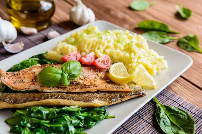 被烘烤的鳟鱼内圆角用土豆泥和蒸的菠菜 免版税库存照片
