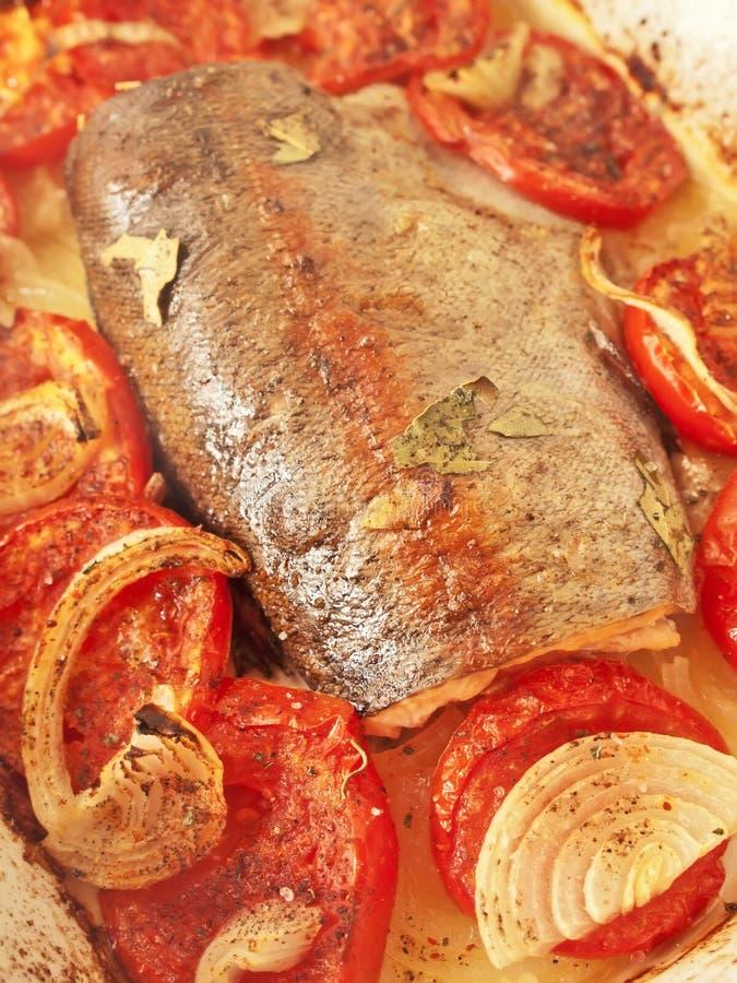 被烘烤的鳟鱼用蕃茄和葱 免版税库存图片