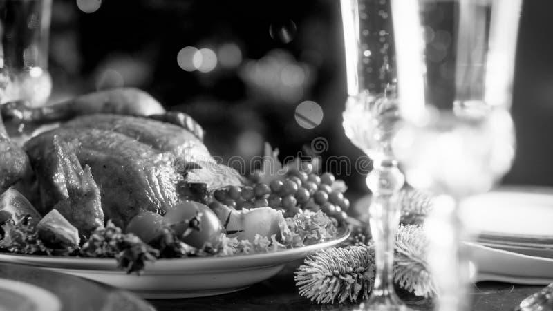 被烘烤的鸡和玻璃的黑白图象用香槟在欢乐餐桌上 免版税库存照片