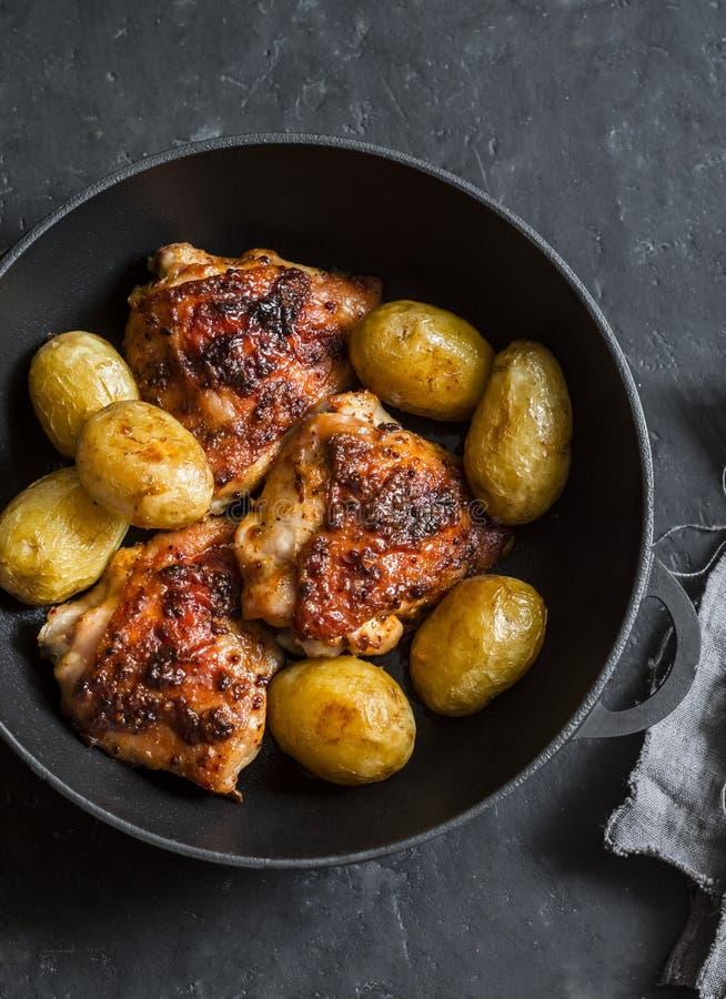 被烘烤的鸡用在平底锅的年轻土豆在黑暗的背景 免版税库存照片