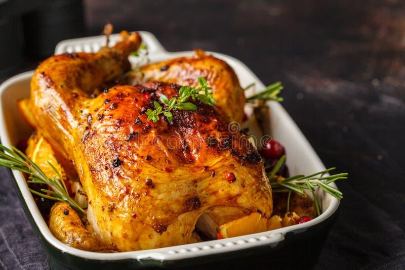 被烘烤的鸡用香料、蔓越桔、桔子和葱在玻璃盘 免版税图库摄影