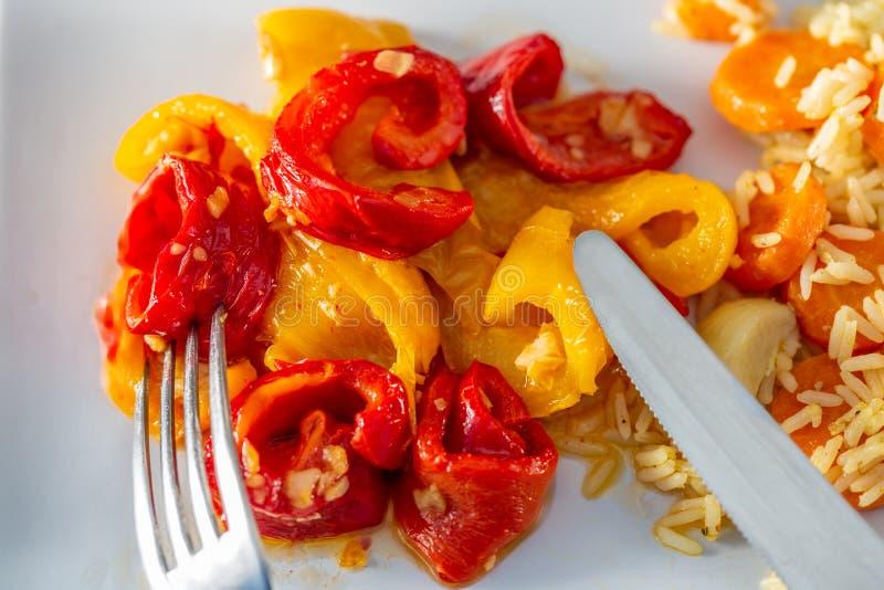 被烘烤的黄色红辣椒和煮熟的白米用可口红萝卜在一块白色陶瓷板材 免版税库存照片