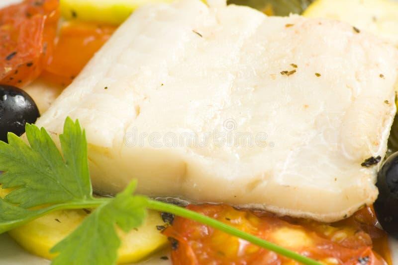 被烘烤的黑色鳕鱼片橄榄蕃茄夏南瓜 库存图片