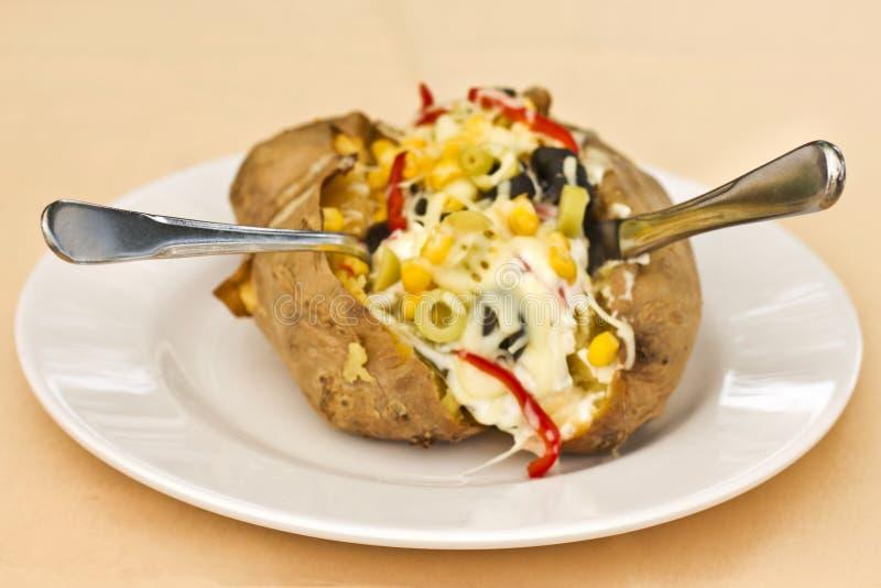 被烘烤的kumpir土豆充塞用乳酪,香肠,橄榄,胡椒 免版税库存照片