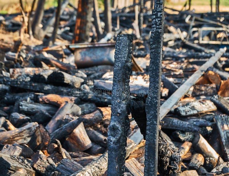 被烧毁的木屋的火灾残骸 有选择地聚焦前黑色木梁,背景故意模糊 免版税库存照片