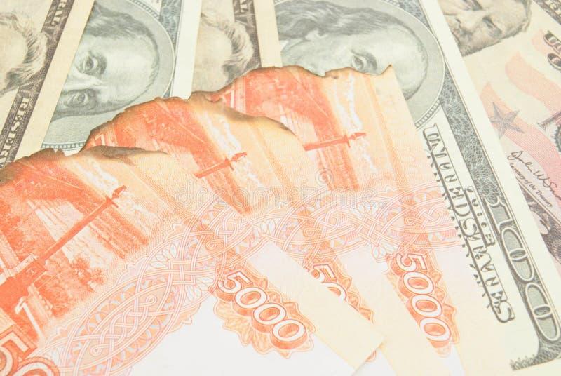 被烧焦的俄罗斯卢布和美元背景 图库摄影