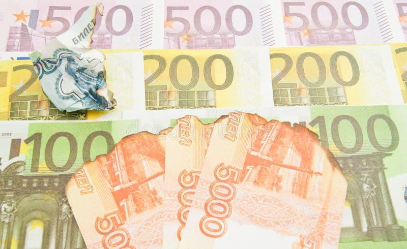 被烧焦的笔记卢布和欧洲钞票 库存图片
