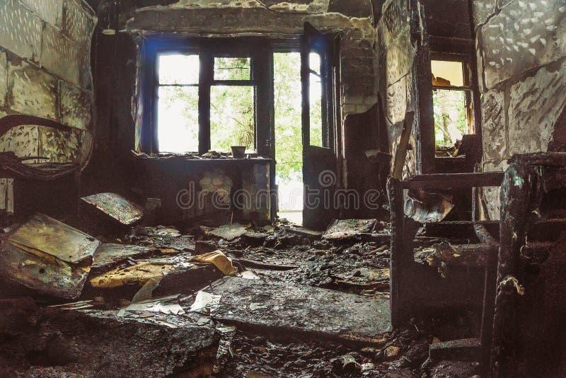 被烧的室在有光的被烧的被放弃的房子里从阳台和窗口 免版税图库摄影