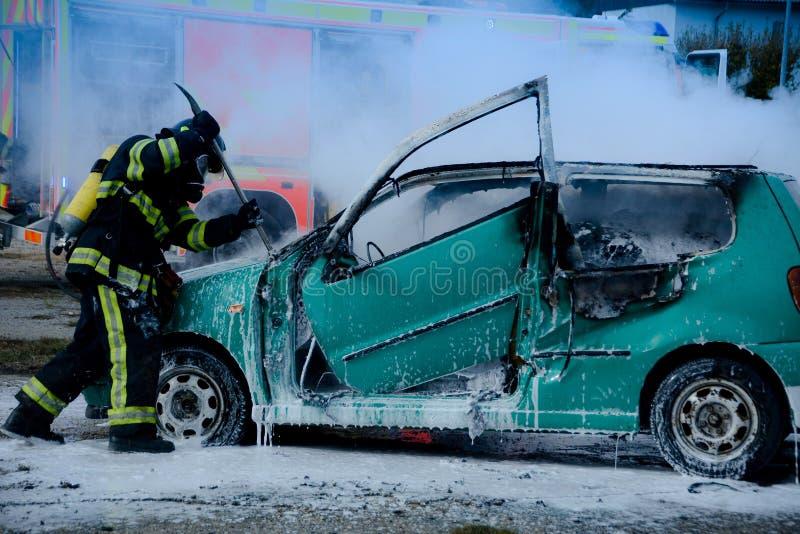 被烧的汽车的消防队员抢救的车祸受害者 免版税图库摄影